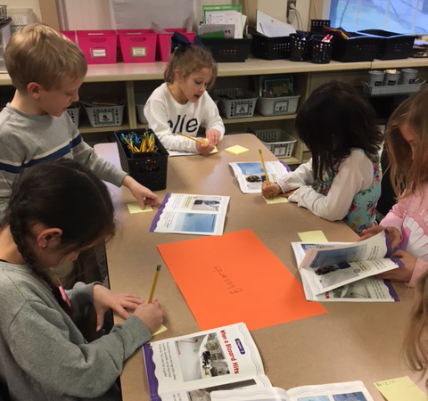 Students work in small groups at a table