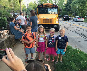 Kids lining up by bus on first day of school